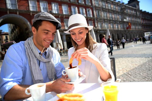 Couple eating chocolate con churros in Plaza Mayor