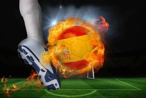 A foot kicking a fire ball colored like the Spanish flag