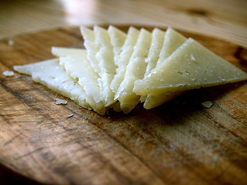 slices of Manchego Cheese over a cutboard